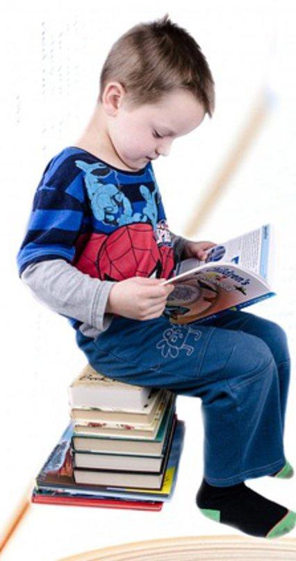 Kind sitzt auf einem Stapel Bücher und liest