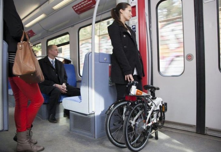 Frau mit Klapprad in der Straßenbahn