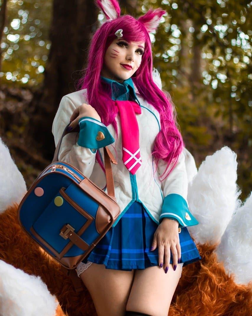 Foto da cosplayer brasileira Sayuki Lola com o cosplay da Ahri Colegial, com um uniforme escolar com uma minissaia listrada azul. A Ahri está com os cabelos rosa e na foto a personagem está segurando uma bolsa.