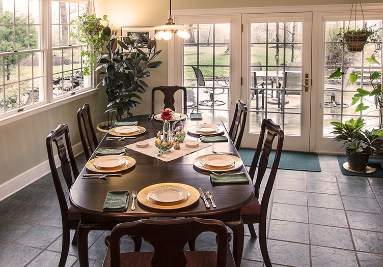 Window lined dining room with table for 6 set with yellow place settings,