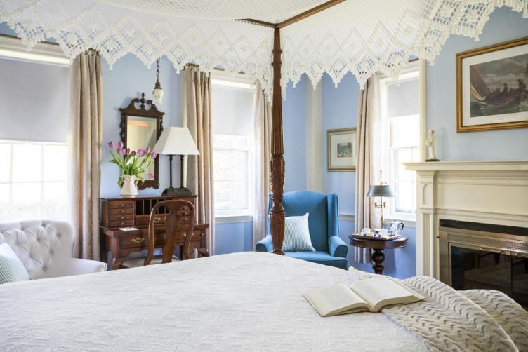 candleberry inn room feature blue walls, four poster bed with white lace canopy blue interior decor