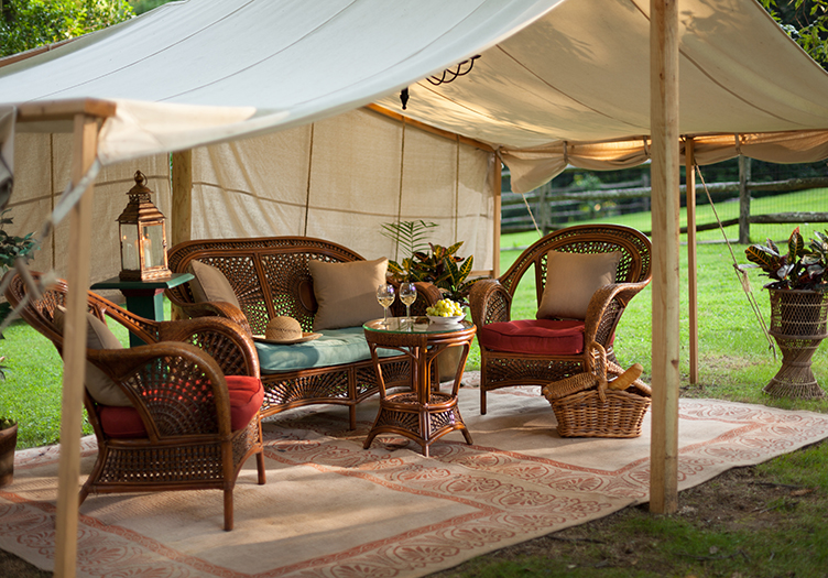 Elegant outside tent on the lawn with wicker furniture, red and cream cushions and rugand