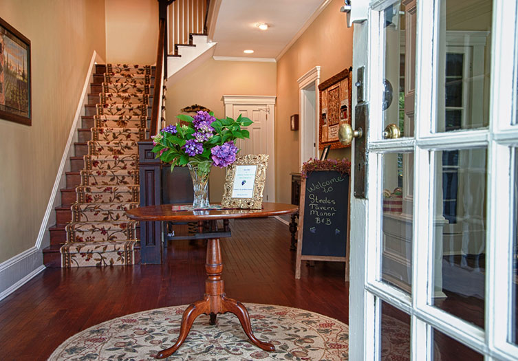 Beautifully decorated foyer entry of the B&B with hardwood floors, center round table, and staircase to the upstairs