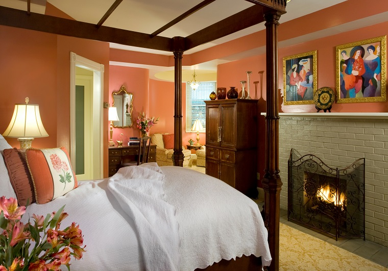 swann house bed and breakfast room 2 with beautiful four poster hardwood bed and salmon walls fireplace beautiful paintings and decor