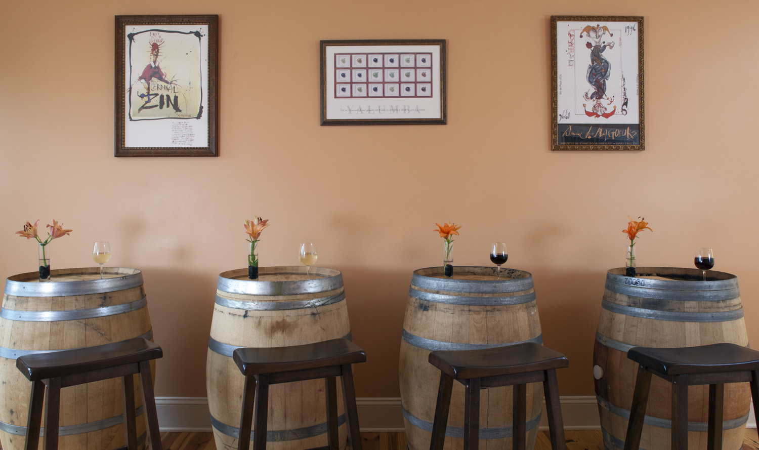 Arcady's barrel room with stools in front of barrels topped with fresh flowers and wine glasses