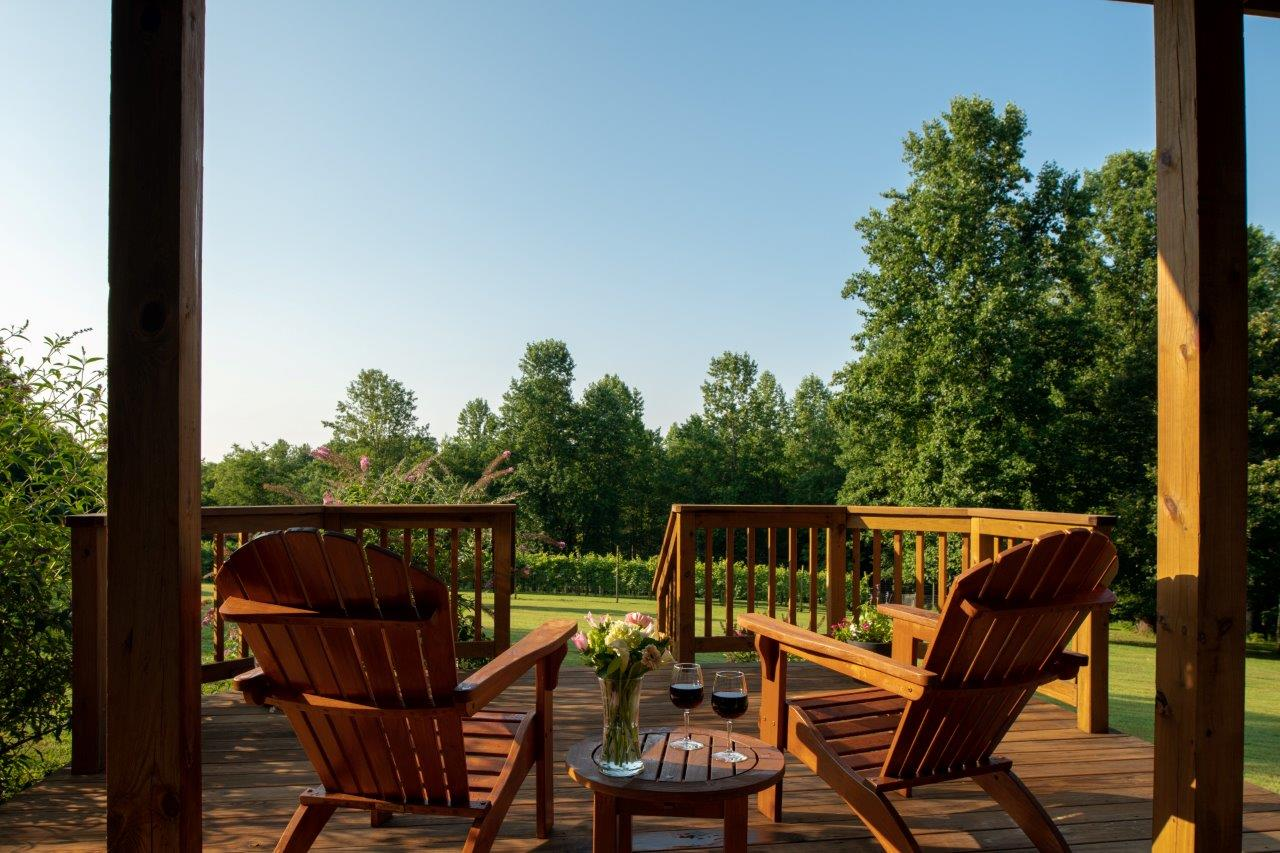 Arcady's Madison Suite deck with wood Adirondack chairs and a table overlooking lush green grass and trees