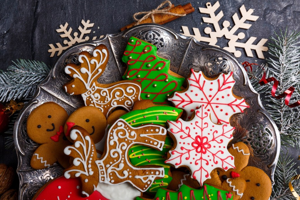 Beautiful and tasty Christmas cookies of different shapes and decorated with colored sugar icing. View from above. Indoors.