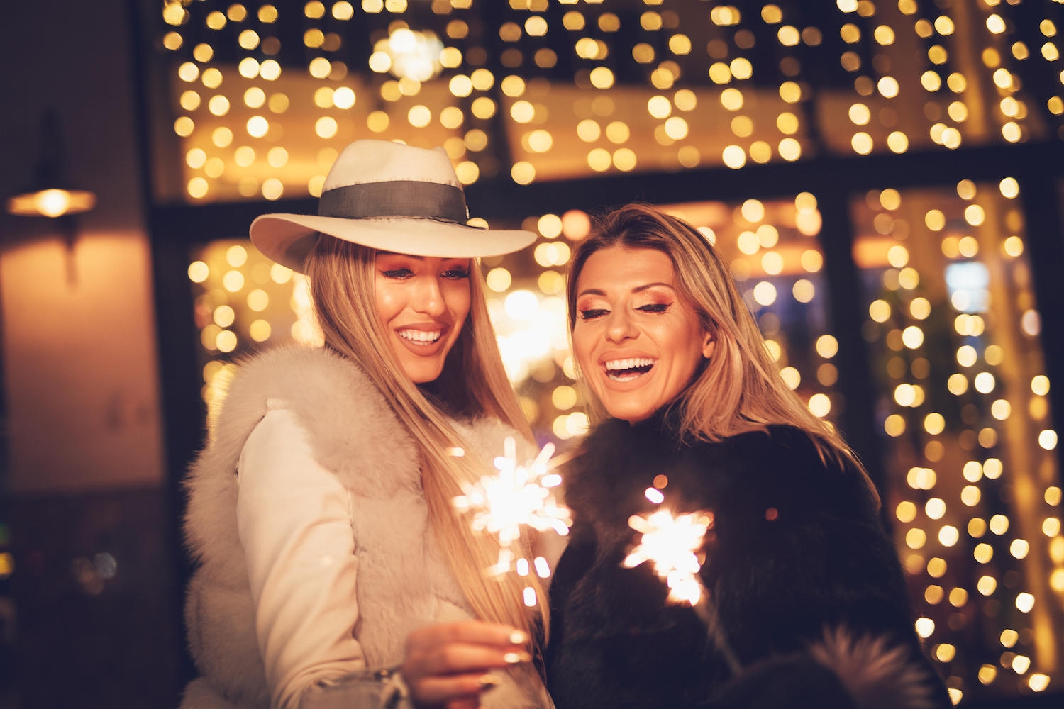 Young beautiful cheerful female friend with sparklers having fun and enjoying in the city street at night at Christmas time. (Young beautiful cheerful couple with sparklers having fun and enjoying in the city street at night