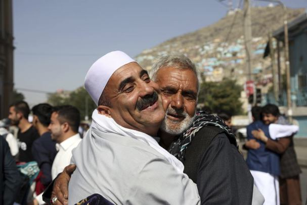 Afghans hug each other after offering Eid al-Fitr prayers outside of Shah-e-Dushamshera mosque in Kabul, Afghanistan, Sunday, June 25, 2017. The three-day holiday marks the end of the holy fasting month of Ramadan. (AP Photo/Rahmat Gul)