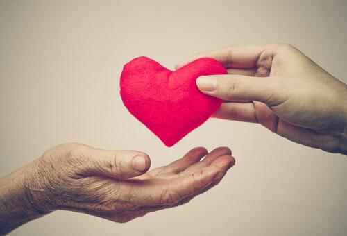 Mano-de-una-persona-joven-dando-corazon-a-mano-de-persona-mayor