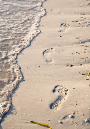 trail of footprints in sand on beach