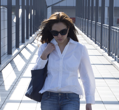 Young woman with sunglasses is walking the overpass