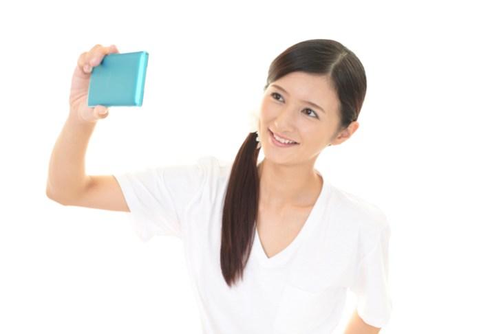 顔を撮影する女性の画像