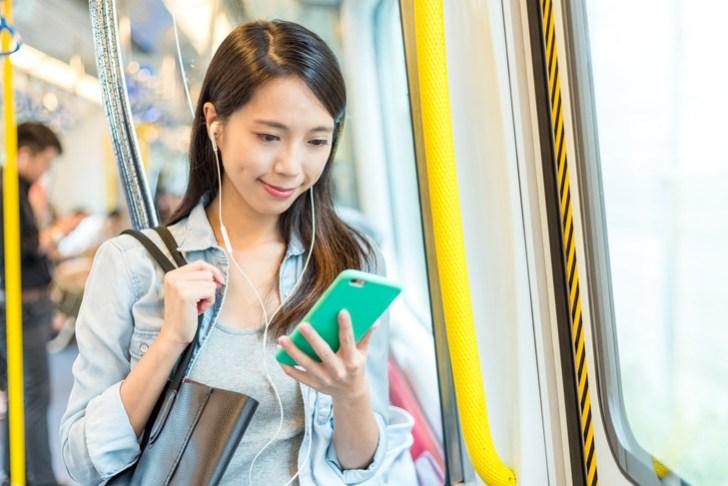電車で立つ女性の画像