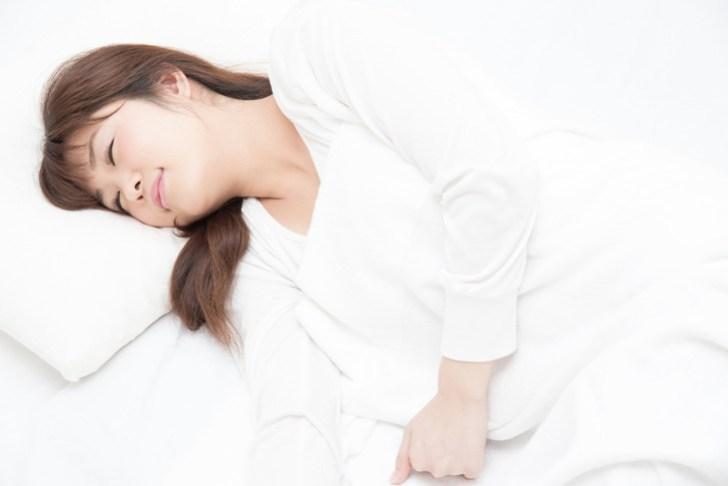 横向きに寝る女性の画像