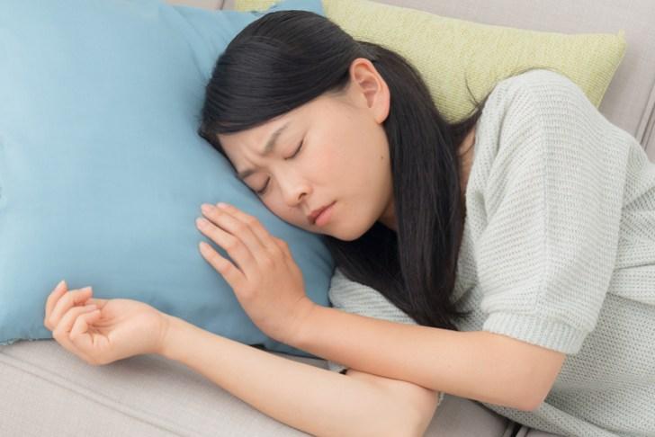 眉間にしわを寄せて寝ている女性の画像