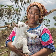 A young lady carrying a goat