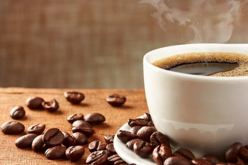 bigstock-coffee-cup-and-coffee-beans-84244856-min
