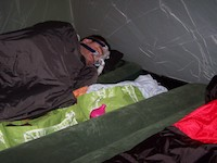 man in sleeping bag wearing CPAP