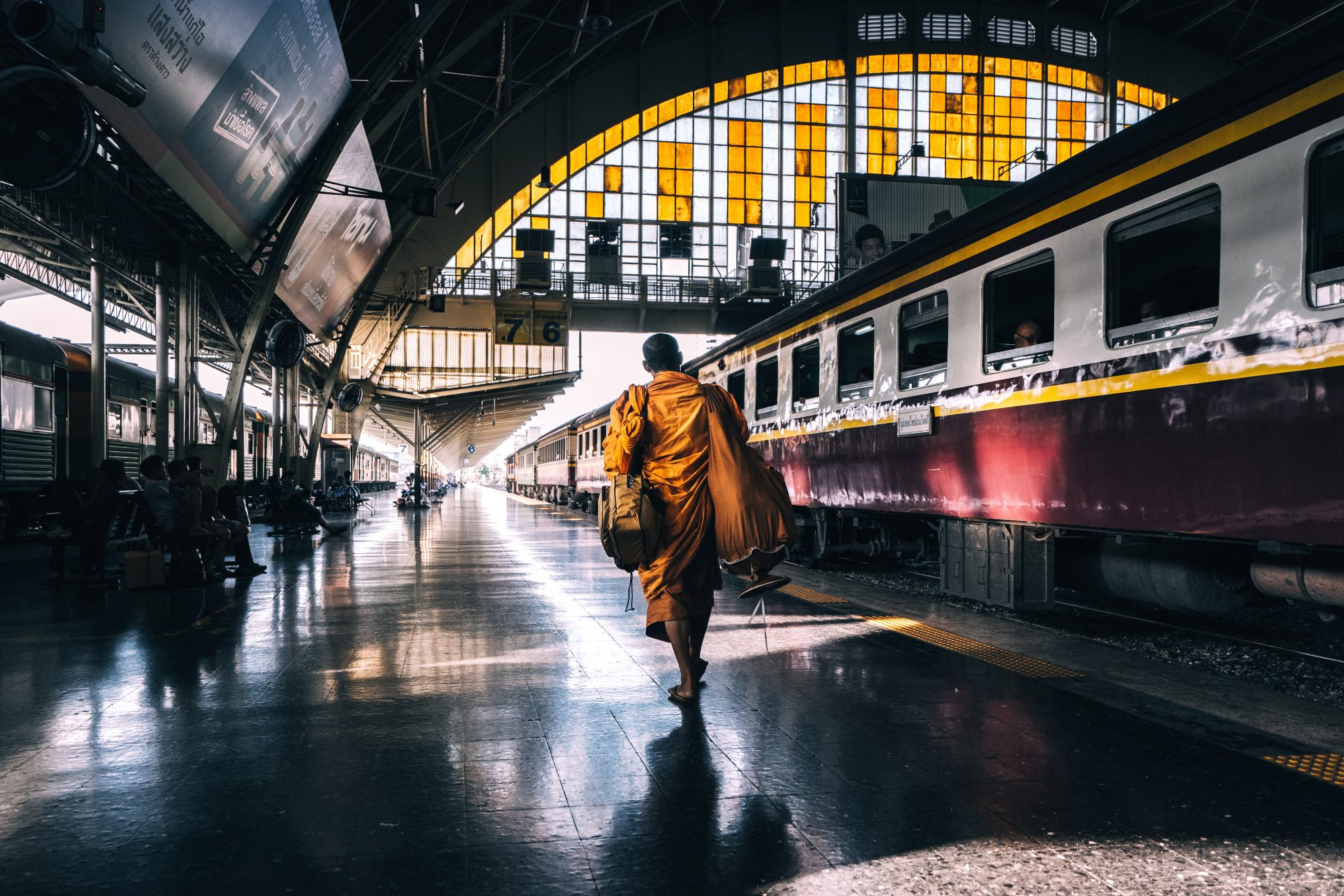 Monk walking on train station platform in Bangkok Thailand on SelfishMe Travel LLC