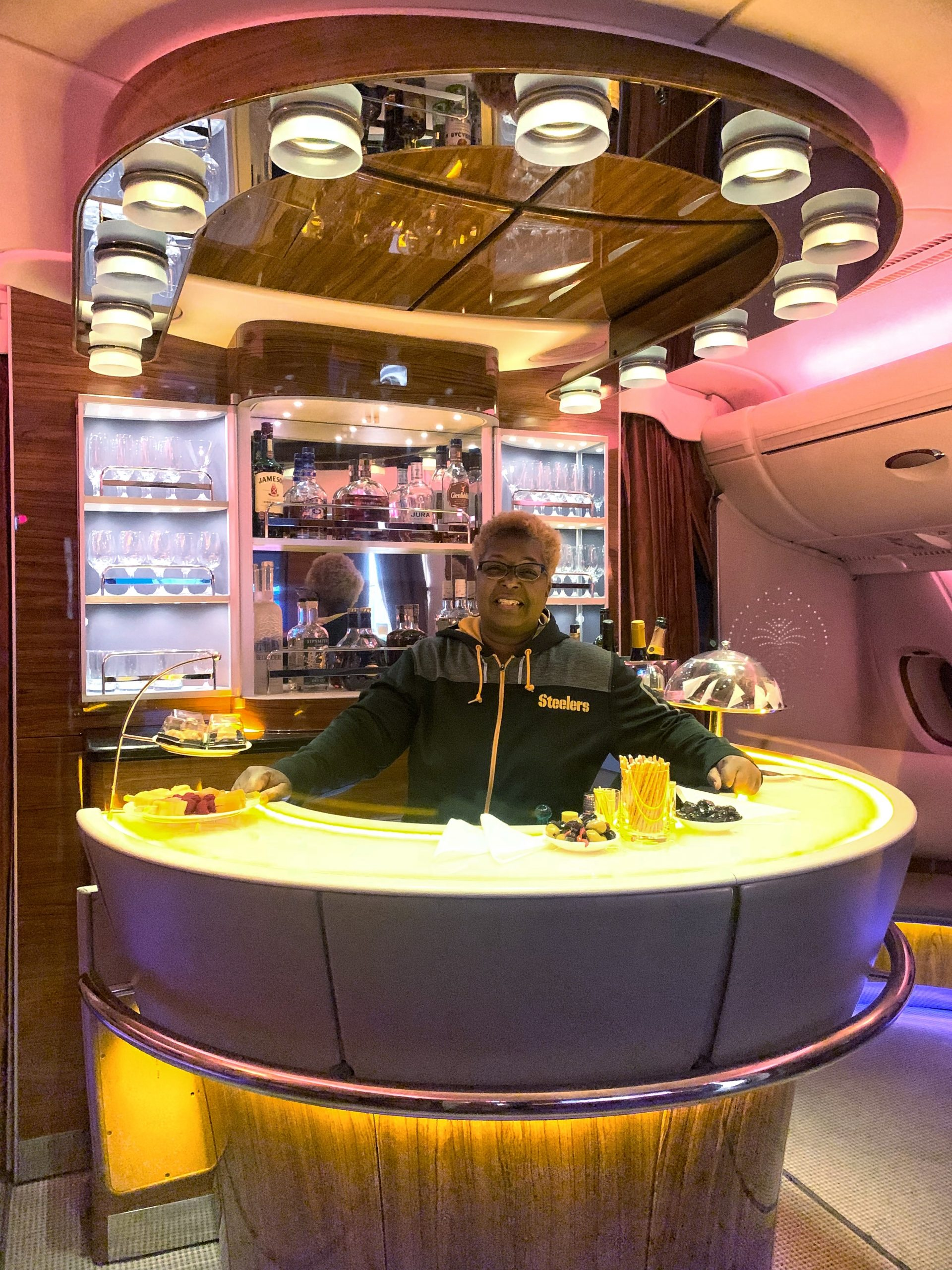 """Danielle Lewis, owner of SelfishMe Travel LLC, at the """"Bar in the Sky"""" on Emirates Airline's Airbus A380 - image taken with an iPhone 7"""