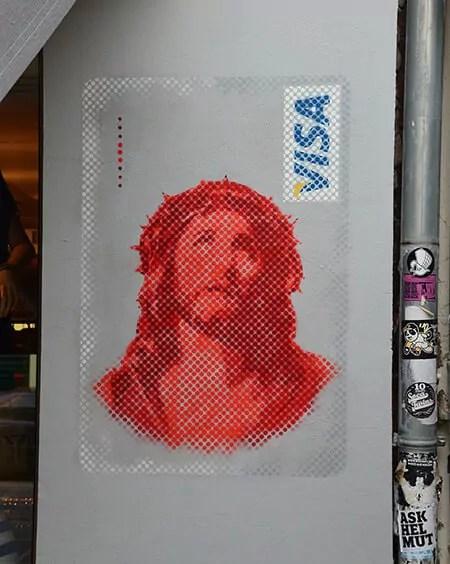 Jesus VISA graffiti- street art in Berlin Kastanienallee von Slava Ostap