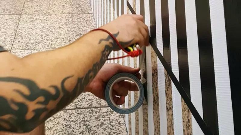 Ostap-Tape-Artist beim Kleben-Die Hände-Nahaufnahme