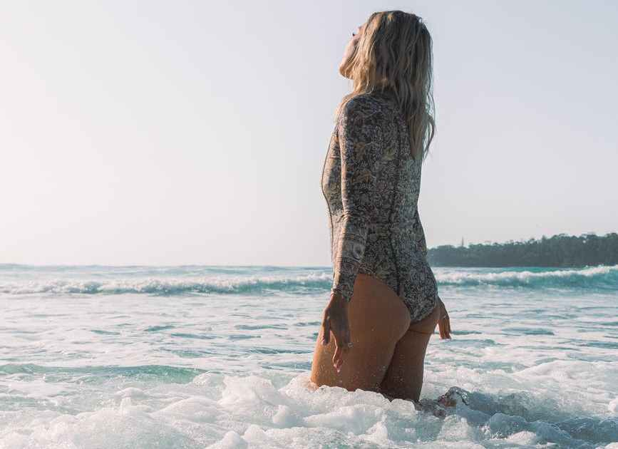 anonymous lady in swimsuit standing in sea