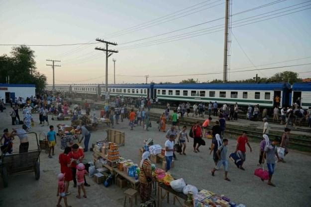 Vendors sell their wares to train passengers in Beyneu