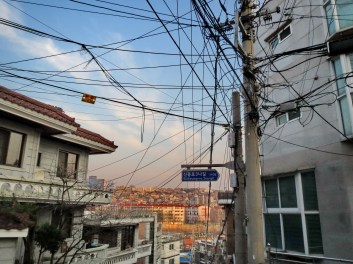 South Korean cities have some of the highest population density in the world. Overhead rats' nests of wiring are everywhere to connect the many small dwellings to phone and electricity.