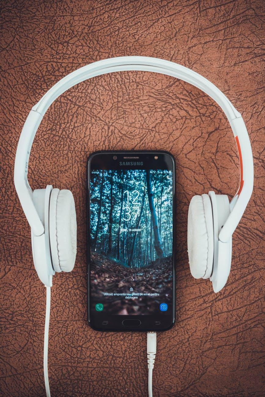 turned on black samsung smartphone between headphones