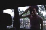 Beggar boy looking in car window