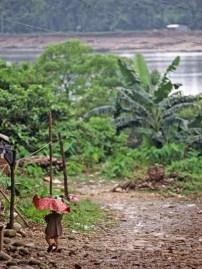 Child walking with red umbrella, border of India and Bangladesh