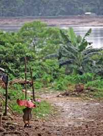 Child walking with red umbrella, border of India and Bangladesh