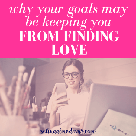 """girl with glasses holding up a smartphone while sitting in front of a laptop with pink overlay and white text that reads, """"Why Your Goals May Be Keeping You From Finding Love"""""""