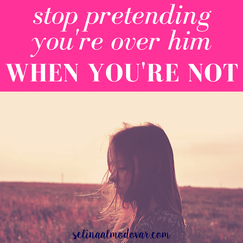 "girl staring down at a field with blank stare while hair blows around her from the wind with pink overlay and white text that reads, ""Stop Pretending You're Over Him When You're Not"""