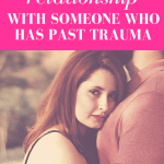 "redhead woman hugging chest of a man while looking into the camera with a solemn face with pink overlay and white text that reads, ""How To Have A Relationship With Someone Who Has Past Trauma"""