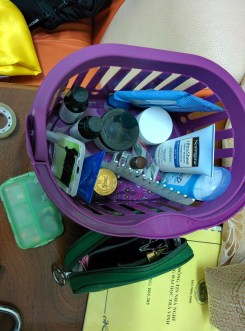 2 (1 not pictured) bottles of sunscreen, 3 (2 not pictured) sticks of deodorant, 3 vials of essential oil: lavender, peppermint, tea tree oil, 1 pack of bobby pins, 1 jar of night cream, 1 comb, 1 jar of tigar balm, 1 case of jewelry, and 1 case of makeup including: moisturizer, travel brushes, eyelash curler, mascara, eye liner, eye shadow, lipstick