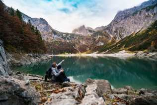Couple sitting at the edge of a lake by mountains