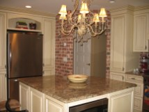 Kitchen with faux brick wall, six burner wolf stove, and radiant heat underfoot.