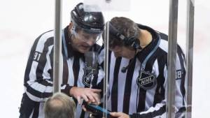 Referees reviewing a play during a coach's challenge
