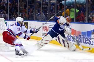 New York Islanders goalie Jaroslav Halak rimming the puck on the boards