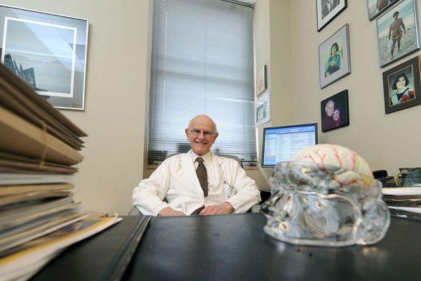 Dr. Charles Tator sitting at his desk