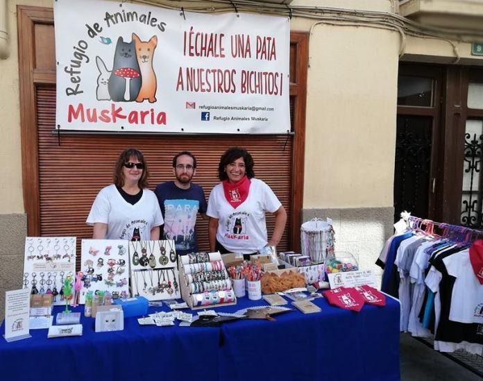 voluntarios en venta de merchandising de Refugio Muskaria
