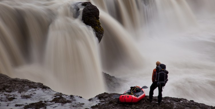 Alastair Humphreys stands with a packraft in front of a waterfall during his trek across Iceland