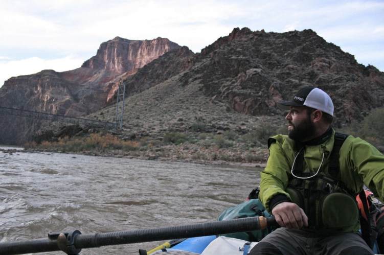 Raymond Pitman rows a raft on the Colorado River just upstream from the Bright Angel Bridge