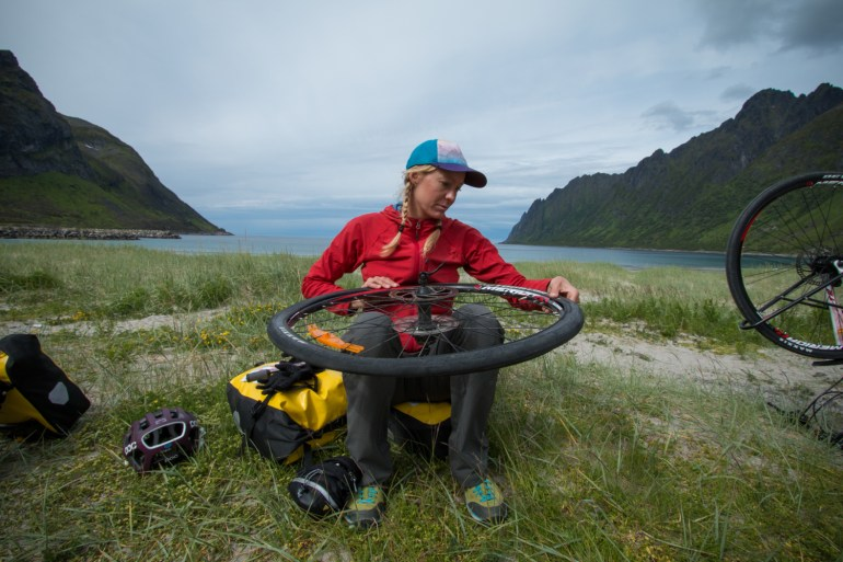Hilary Oliver fixes a flat tire at a beach on the first day of a bike tour in northern Norway.