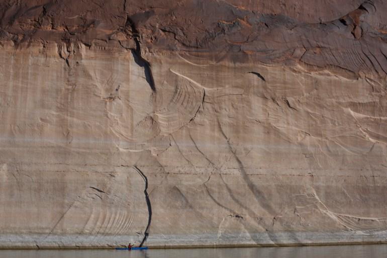 a kayaker beneath the bathtub ring in glen canyon