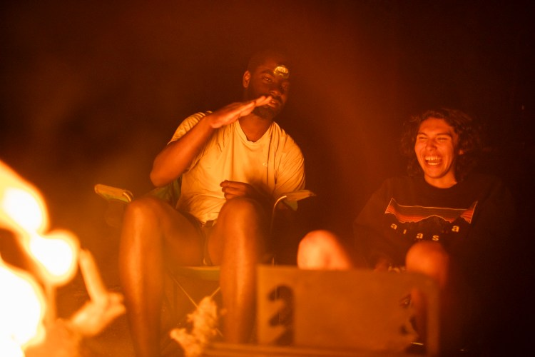 forest woodward photo of two campers joking and laughing around fire