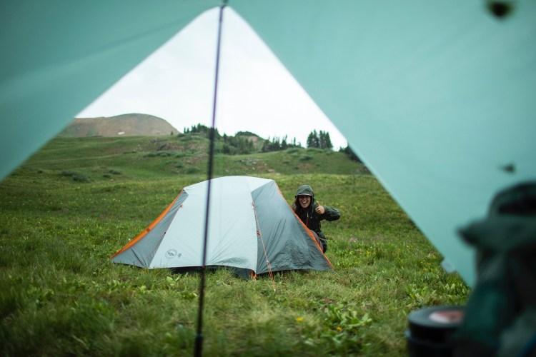 forest woodward photo of a woman next to a tent in the rain